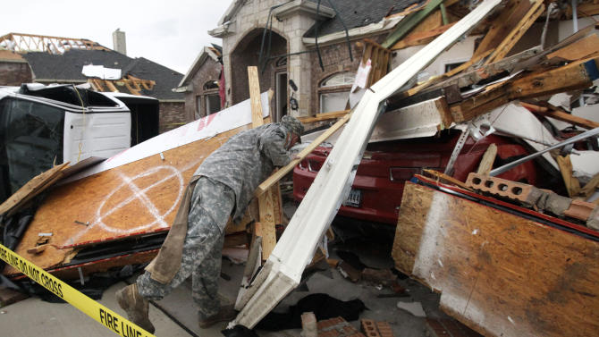 Texas Army National Guard Cpl. Brock Fischer of Charlie Troop, 3-124 Cav., searches a vehicle in front of a tornado damaged home Tuesday, April 3, 2012, in Forney, Texas. Tornadoes tore through the Dallas area Tuesday, peeling roofs off homes, tossing big-rig trucks into the air and leaving flattened tractor trailers strewn along highways and parking lots. (AP Photo/Tony Gutierrez)