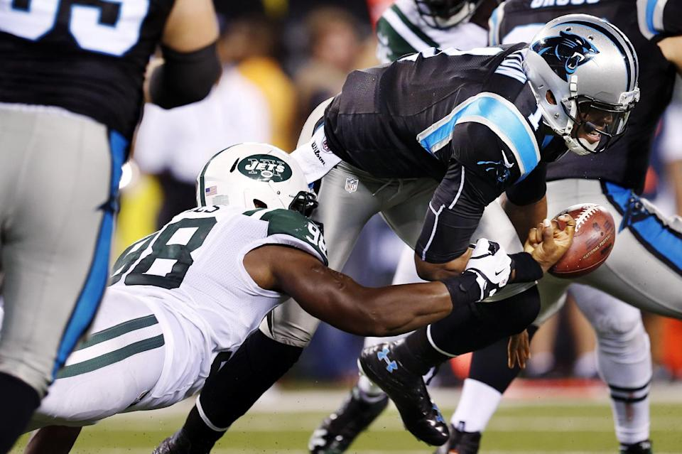 New York Jets defensive end Quinton Coples (98) knocks the ball away from Carolina Panthers quarterback Cam Newton (1) during the first half of a preseason NFL football game, Sunday, Aug. 26, 2012, in East Rutherford, N.J. (AP Photo/Julio Cortez)