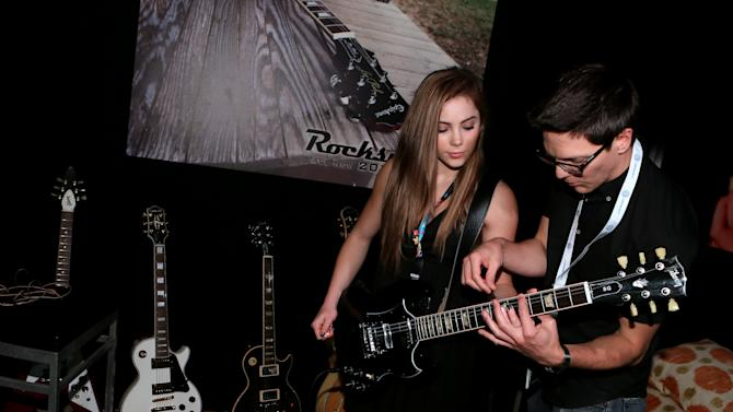 """McKayla Maroney, left, plays """"Rocksmith 2014"""" at the Ubisoft booth at E3 on Wednesday, June 12, 2013, in Los Angeles. (Photo by Alexandra Wyman/Invision for Ubisoft/AP Images)"""