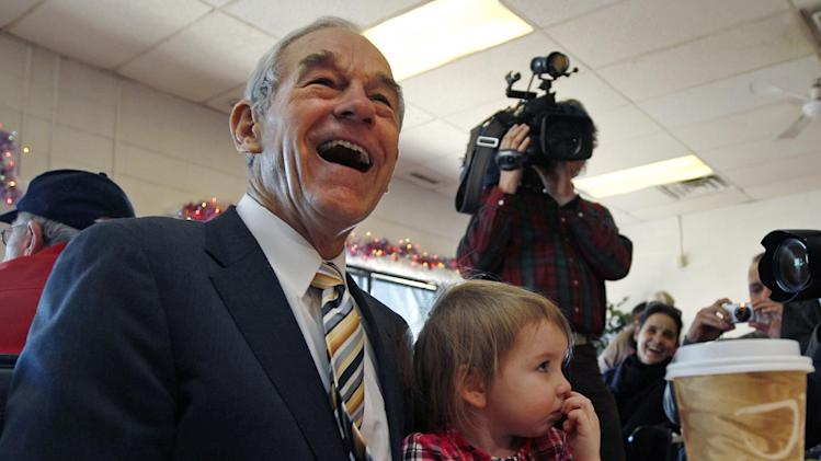 Republican presidential candidate Rep. Ron Paul, R-Texas, laughs as he sits down with Elizabeth Rose Chamberlain, 3, of Epping, N.H., while campaigning at the Early Bird Cafe in Plaistow, N.H., Tuesday Dec. 20, 2011. (AP Photo/Charles Krupa)