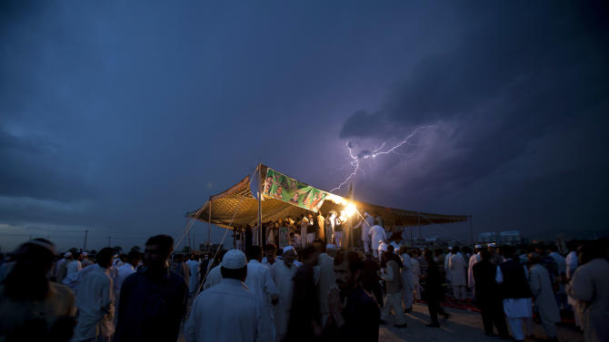 Lightning flashes as political supporters of the Pakistan Muslim League hold a meeting under tight security due to ongoing attacks on political rallies and parties' election offices, in Islamabad, Pakistan on Friday, April 26, 2013. The Muttahida Qaumi Movement has ordered the closure of election offices in Karachi following a blast that killed many party workers. (AP Photo/B.K. Bangash)