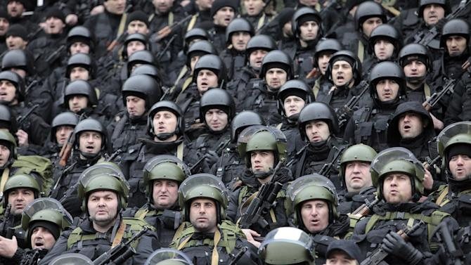 """Chechen special forces listen to Chechnya's regional leader Ramzan Kadyrov deliver a speech in Grozny, Russia, Sunday, Dec. 28, 2014. About 20,000 armed security forces attended a rally at a stadium in Grozny. Kadyrov said that Chechens could serve as """"volunteers"""" to perform military tasks that the Russian armed forces can't fulfill. (AP Photo/Musa Sadulayev)"""