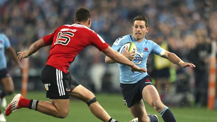 Waratahs' Bernard Foley, right, tries to sidestep the defense of Crusaders' Israel Dagg during their Super Rugby final in Sydney, Australia, Saturday, Aug. 2, 2014.(AP Photo/Rob Griffith)