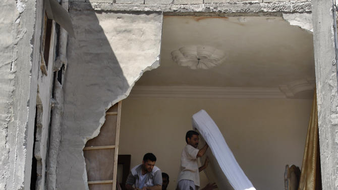 Syrians salvage what they can of their belongings from a building that was hit during a Syrian government airstrike in Aleppo, Syria, Sunday, Aug. 19, 2012 (AP Photo/ Khalil Hamra)