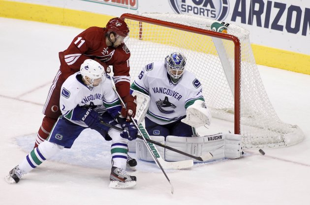 Canucks' Schneider deflects a shot by the Coyotes during their NHL game in Glendale.