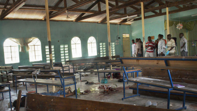 Bodies of some of those killed in the attack lie on the ground underneath church pews inside the African Inland Church, in Garissa, Kenya Sunday, July 1, 2012. Gunmen killed two policemen guarding a church, snatched their rifles and then opened fire on the congregation with bullets and grenades on Sunday, killing at least 10 people and wounding at least 40, security officials said, with militants from Somalia being immediately suspected. (AP Photo/Chris Mann)