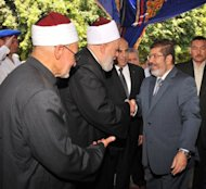 In this handout picture made available by the Egyptian presidency, president-elect Mohamed Morsi (right) shakes hands with Egyptian Grand Mufti Ali Gomaa (centre) and other Muslim clerics upon his arrival at Cairo's historic Al-Azhar mosque to attend weekly prayers on the eve of his swearing-in as Egypt's first civilian president