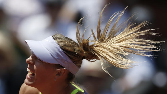 Russia's Maria Sharapova's hair flies as she serves against Serbia's Jelena Jankovic in their quarterfinal match at the French Open tennis tournament, at Roland Garros stadium in Paris, Wednesday June 5, 2013. (AP Photo/Petr David Josek)