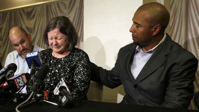 Former NFL player Dorsey Levens, right, extends a hand as Mary Ann Easterling, the widow of former NFL player Ray Easterling, reacts as former NFL player Kevin Turner, left, looks on during a news conference, Tuesday, April 9, 2013, in Philadelphia, after a hearing to determine whether the NFL faces years of litigation over concussion-related brain injuries. Thousands of former players have accused league officials of concealing what they knew about the risk of playing after a concussion. The lawsuits allege the league glorified violence as the game became a $9 billion-a-year industry. (AP Photo/Matt Rourke)