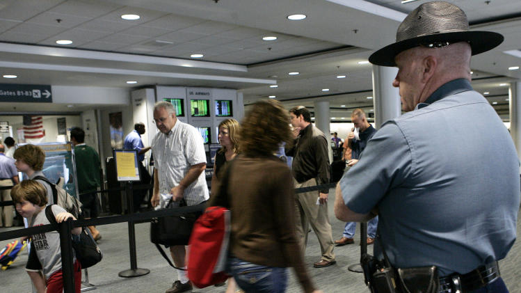 FILE - In this Thursday, Aug. 10, 2006 file photo, a Massachusetts state trooper keeps watch over travelers making their way through Logan International Airport in Boston. Transportation Security Administration officers at Boston's Logan International Airport are alleging that a program intended to help flag possible terrorists based on passengers' mannerisms has led to rampant racial profiling, the New York Times reported Saturday, Aug. 11,2012.(AP Photo/Elise Amendola, File)