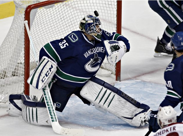 The puck goes past Canucks goalie Schneider into the net off the stick of Coyotes' Boedker during NHL hockey in Vancouver