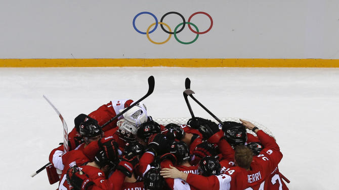 Canada's players huddle as they celebrate defeating Sweden in their men's ice hockey gold medal game at the Sochi 2014 Winter Olympic Games
