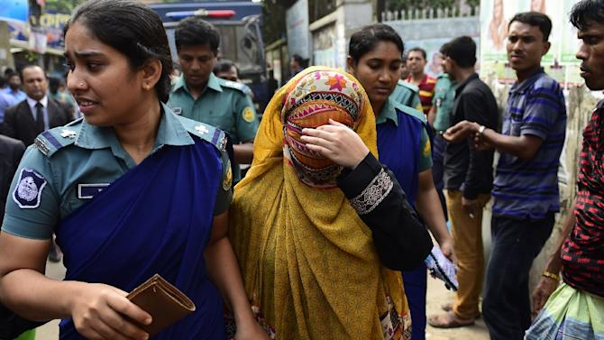 Bangladeshi security personnel escort Nritto Shahadat -- the wife of Shahadat Hossain -- towards the courthouse in Dhaka, on October 4, 2015