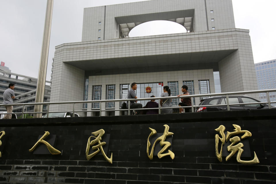 People stand at the Hefei City Intermediate People's Court Wednesday, Aug. 8, 2012  in Hefei, Anhui Province, China. The murder trial of Gu Kailai, wife of ousted Chinese politician Bo Xilai,  will start Thursday. (AP Photo/Eugene Hoshiko)