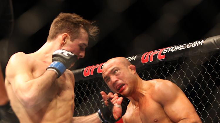 BJ Penn, right, takes a punch from Rory MacDonald during their mixed martial arts bout at a UFC on FOX 5 event in Seattle, Saturday, Dec. 8, 2012. MacDonald won via unanimous decision. (AP Photo/Gregory Payan)