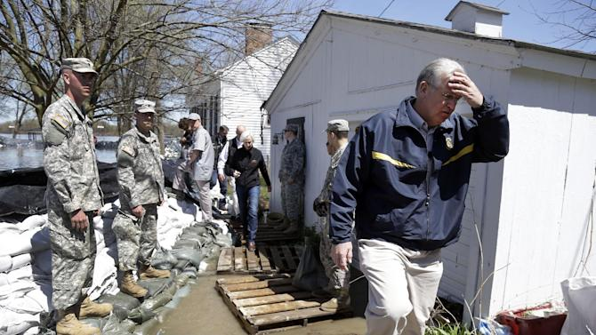 Missouri Gov. Jay Nixon, right, walks away from floodwaters after meeting with members of the Missouri National Guard as they make flood preparations Saturday, April 20, 2013, in Clarksville, Mo. Communities along the Mississippi River and other rain-engorged waterways are waging feverish bids to hold back floodwaters that may soon approach record levels. (AP Photo/Jeff Roberson)