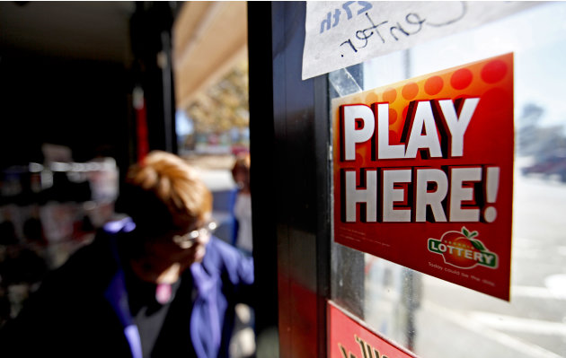 A sign on a doorway advertises the Georgia Lottery as a customer enters a convenience store, Monday, Nov. 26, 2012, in Atlanta. As the Powerball jackpot soars, a Georgia Lottery official says the agen