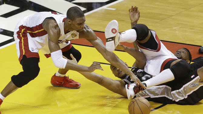Miami Heat center Chris Bosh (1) Miami Heat power forward Udonis Haslem (40) and San Antonio Spurs center Boris Diaw (33) of France, vie for loose ball during the second half of Game 1 of the NBA Finals basketball game, Thursday, June 6, 2013 in Miami. The San Antonio Spurs won 92-88. (AP Photo/Wilfredo Lee)