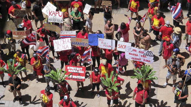 FILE - In this April 21, 2015 file photo, protesters opposed to the construction of the Thirty Meter Telescope gather outside the Hawaii Legislature in Honolulu. Hawaii County top prosecutor Mitch Roth said Friday, May 29, 2015 that he will dismiss charges against about 10 of the 31 protesters who were arrested while blocking construction of a giant telescope on Mauna Kea. The remaining people arrested last month were charged with obstruction of government operations. (AP Photo/Cathy Bussewitz, File)