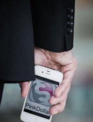 Paul Ramscar holds a smartphone displaying the Pink Dollar app logo in Hong Kong. A new smartphone app aims to put members of the lesbian, gay, bisexual and transgender community in touch with businesses deemed friendly to sexual minorities in socially conservative Hong Kong