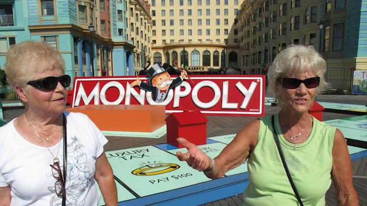 In this Sept. 13, 2011 photo, France Duff, left, of Wellham, Canada, and Shirley Theal, right, of Niagara Falls, Canada, stand in front of a life-sized Monopoly board that caught their attention on the Atlantic City Boardwalk in Atlantic City, N.J. Atlantic City once had a monopoly on casino gambling on the East Coast, but will have to fight in 2012 as never before against competition from casinos all around it. (AP Photo/Wayne Parry)