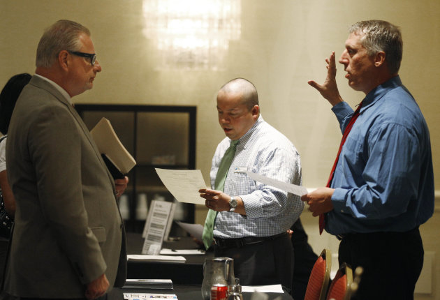 In this June 18, 2012, photo, Dave Eisley, right, Commercial Sales Manager for Alarm Detection Systems inc. speaks with job candidate, Mike Tuchel, left, during a career fair in Oak Brook, Ill. A survey of chief executives released Wednesday, June 20, 2012, shows fewer large U.S. companies plan to hire or boost spending in the next six months, reflecting a weaker U.S. economy. (AP Photo/M. Spencer Green)