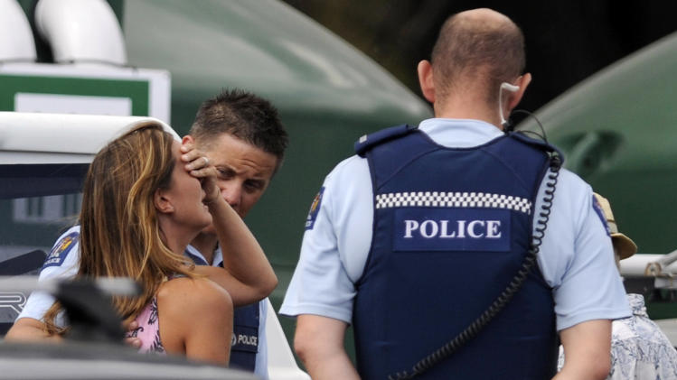 "Police comfort a woman believed to be a family member of a man attacked by a shark at  Muriwai Beach near Auckland, New Zealand, Wednesday, Feb. 27, 2013. Police said a man was found dead in the water after being ""bitten by a large shark."" (AP Photo/Ross Land) NEW ZEALAND OUT, NO SALES"
