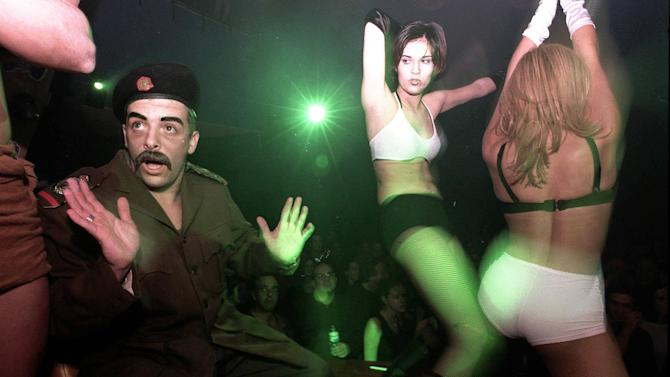 FILE - In this Friday, Feb. 20, 19988 file photo, a Saddam Hussein lookalike wearing a uniform dances with two scantily dressed women who were trying to disarm him during a party in Tel Aviv. The freewheeling seaside oasis of Tel Aviv has long served as an escape from the troubles of everyday Israel. Thanks partly to its vibrant nightlife and balmy climate, it's also developed an international reputation as a fun place to visit _ and one of the few places in the Middle East where gays feel free to walk hand-in-hand and kiss in public. Now, for the first time ever,Tel Aviv is also the target of Iranian-made rockets fired by Hamas militants in the Gaza Strip. (AP Photo/Eyal Warshavsky, File)