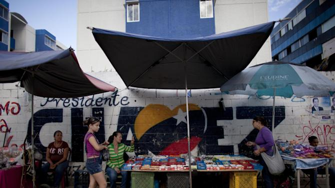 "Street vendors work in front of a mural that reads ""Chavez"" regarding to Venezuela's president Hugo Chavez in Caracas, Venezuela, Tuesday, Dec. 18, 2012. Chavez is recovering in Cuba from a surgery, his fourth operation related to his pelvic cancer since June 2011. (AP Photo/Ariana Cubillos)"