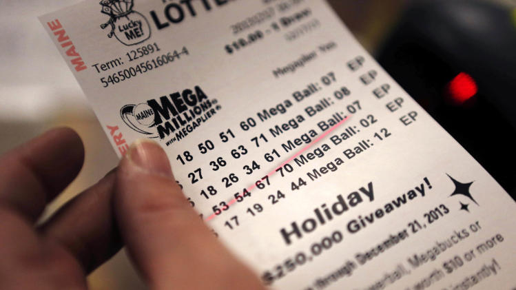 A cashier holds a Mega Millions lottery ticket at a convenience store in Lisbon, Maine, Tuesday, Dec. 17, 2013. With tickets selling well, the jackpot for tonight's drawing is now at an estimated $636 million, the second-biggest lottery prize in U.S. history. (AP Photo/Robert F. Bukaty)