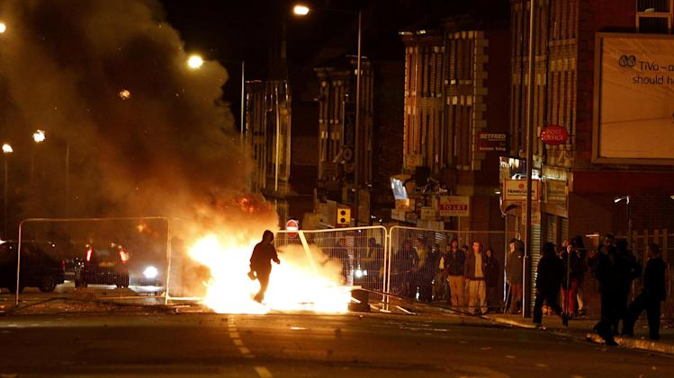 A rioter walks through a burning barricade in the Toxteth area of Liverpool on Wednesday August 10, 2011. In the northern city of Liverpool, about 200 youths hurled missiles at police in a second night of unrest. (AP Photo/PA,  Peter Byrne)  UNITED KINGDOM OUT