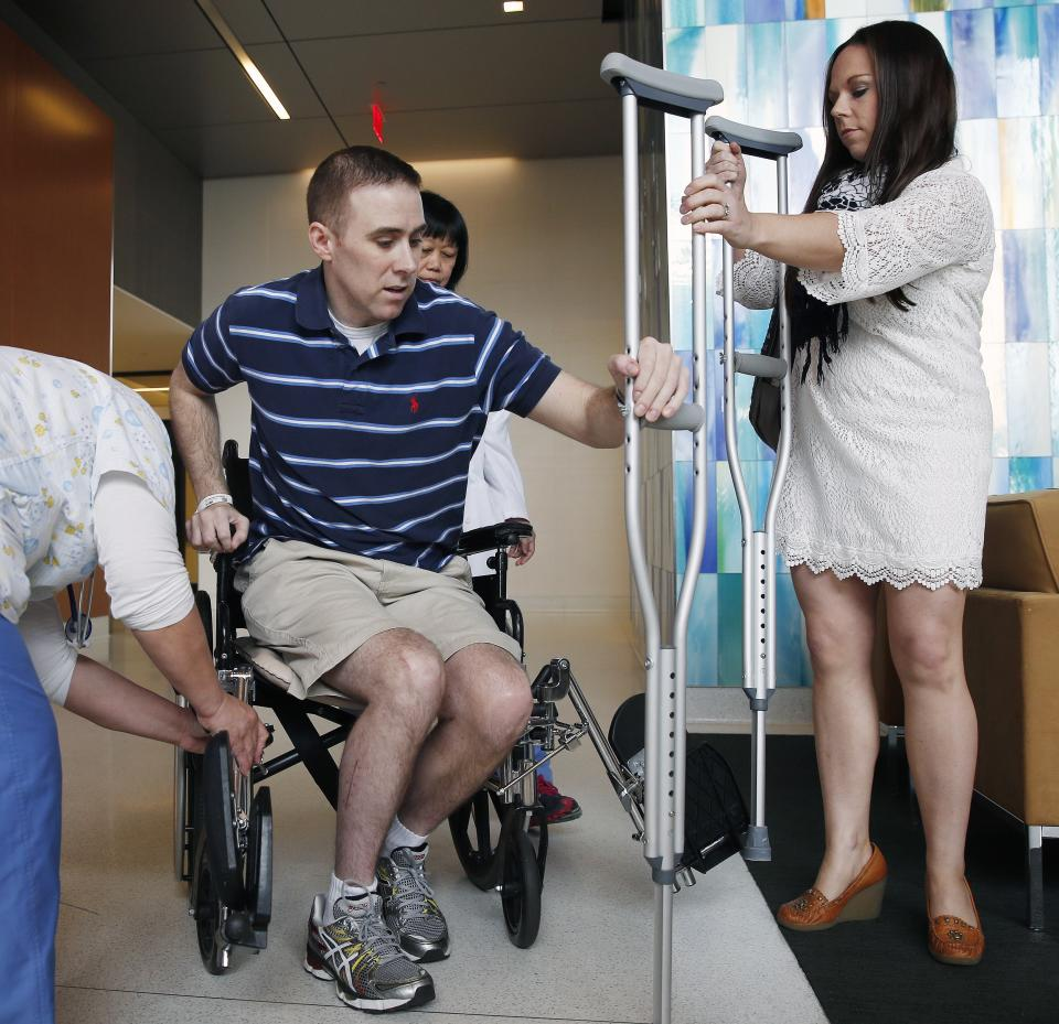 Transit police officer Richard Donohue, left, takes a crutch from his wife Kim as he prepares to leave Spaulding Rehabilitation Hospital in Boston, Friday, June 14, 2013. Donohue was injured during  a shoot-out with the Boston Marathon bombing suspects. (AP Photo/Michael Dwyer)