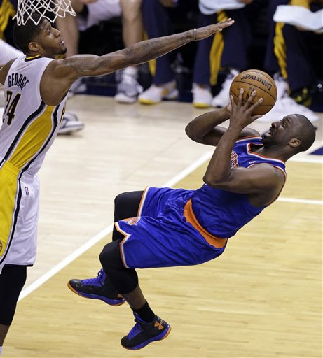 New York Knicks guard Raymond Felton, right, shoots under Indiana Pacers forward Paul George during the third quarter of Game 6 of the Eastern Conference semifinal NBA basketball playoff series in Ind