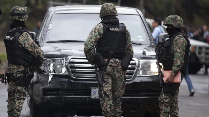 Military guards stand in front of an armored U.S. Embassy vehicle attacked by unknown assailants on the highway leading to the city of Cuernavaca, near Tres Marias, Mexico, Friday, Aug. 24, 2012. Two U.S. government employees were shot and wounded in an attack on their vehicle south of Mexico City on Friday, a law enforcement official said. (AP Photo/Alexandre Meneghini)