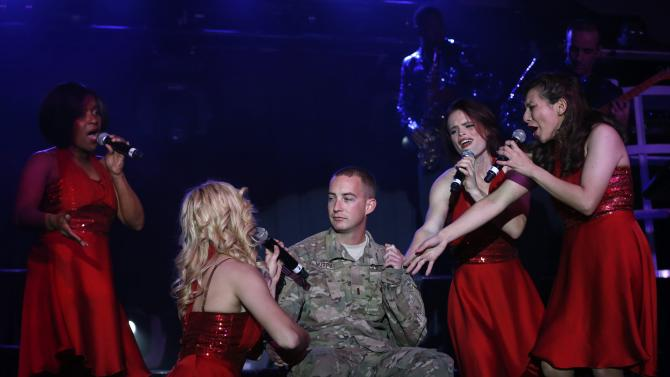 U.S. soldier from the Nato-led International Security Assistance Force sits as performers from United States sing and dance during a Christmas day concert for U.S. military personnel at Bagram Airfield