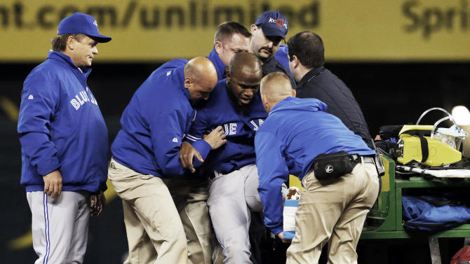 Toronto Blue Jays manager John Gibbons, left, watches as trainers help Blue Jays' Jose Reyes onto a cart during the sixth inning of a baseball game against the Kansas City Royals at Kauffman Stadium in Kansas City, Mo., Friday, April 12, 2013. (AP Photo/Orlin Wagner)