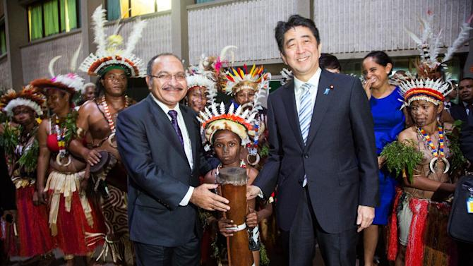 Japan's Prime Minister Shinzo Abe (right) and with Papua New Guinea Prime Minister Peter O'Neil join locals playing the drums before attending an offical dinner at the Papua New Guinea Parliament in Port Moresby on July 10, 2014