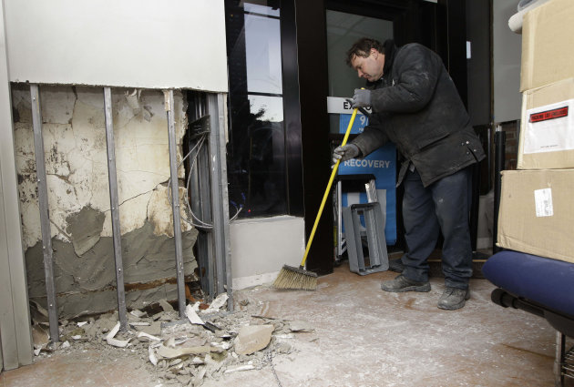 Damage caused by flooding from from Superstorm Sandy is visible inside the visitor center at the World Trade Center Memorial as Ardian Frangaj sweeps up, Monday, Nov. 5, 2012, in New York.  Joe Daniel