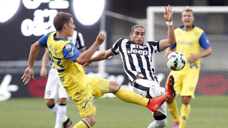 Juventus' Caceres fights for the ball with Chievo Verona's Birsa during their Italian Serie A soccer match in Verona