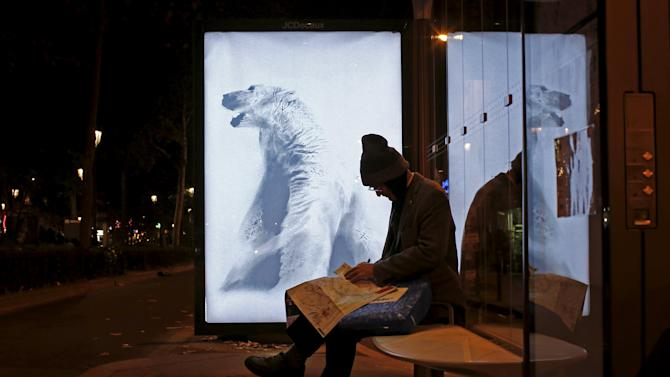 "A poster by street artist Aaron Li-Hill as part of the ""Brandalism"" project is displayed at a bus stop in Paris"