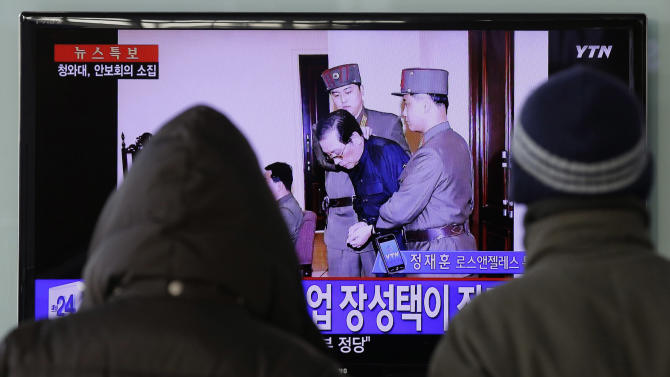 """FILE - In this Dec. 12, 2013 file photo, people watch a TV news report about the execution of Jang Song Thaek, the uncle of North Korean leader Kim Jong Un, at Seoul Railway Station in Seoul, South Korea. The letters on the left top, read """"North Korea Executed Jang Song Thaek after trial."""" The stunning execution of Kim Jong Un's powerful uncle strips China of its most important link to North Korea's leadership and deepens concerns over how the unruly neighbor will proceed on Beijing's key issues of nuclear disarmament and economic reform.(AP Photo/Lee Jin-man, File)"""