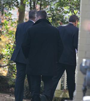 Former CIA Director Gen. David Petraeus, right, followed by security agents, enters his home in Arlington, Va., Friday, Nov. 16, 2012, after testifying on Capitol Hill before closed-door sessions of the Senate and House Intelligence Committees regarding the Sept. 11, 2012 attack of the US embassy in Libya. (AP Photo/Luis M. Alvarez)