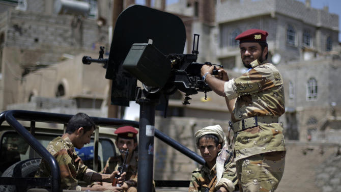 A defected Yemeni army soldier, right, looks on as he stands guard on a vehicle with others next to the site of a demonstration by anti-government protestors demanding the resignation of Yemen's President Ali Abdullah Saleh in Sanaa, Yemen, Monday, Sept. 5, 2011. (AP Photo/Hani Mohammed)