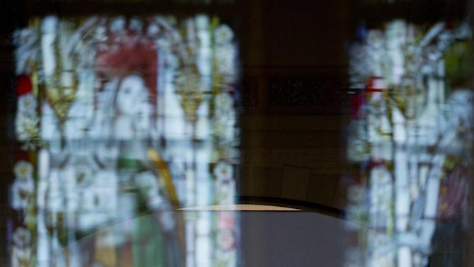Glass stained windows are reflected in doors leading to Dutch master Rembrandt's The Night Watch painting, rear, during a press preview of the renovated Rijkmuseum in Amsterdam, Thursday, April 4, 2013. The Rijksmusuem, home of Rembrandt's Night Watch and other national treasures, is preparing to reopen its doors on April 13 2013 after a decade-long renovation. (AP Photo/Peter Dejong)