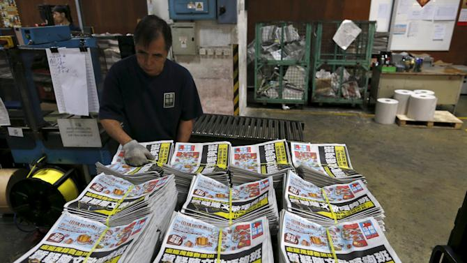 Bundles of the Apple Daily newspaper, published by Next Media Ltd, sit ready for distribution at the company's printing facility in Hong Kong, China