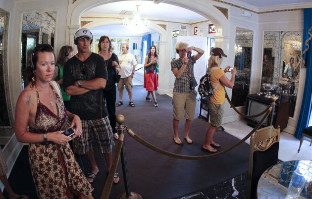 FILE -- This Aug. 2010 photo shows tourists viewing the dining room at Graceland, Elvis Presley's home in Memphis, Tenn. Graceland opened for tours on June 7, 1982. They sold out all 3,024 tickets on the first day and didn't look back, forever changing the Memphis tourist landscape while keeping Elvis and his legend alive.(AP Photo/Mark Humphrey)