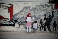 Bahraini children hold up pictures of tortured democracy activists as they pose in front of graffiti depicting a scene of anti-government demonstrations in the Shiite village of Barbar on the western outskirts of the Gulf kingdom Violence marred Bahrain's controversial Grand Prix race as a fire bomb exploded near Force India team members and protesters clashed with police