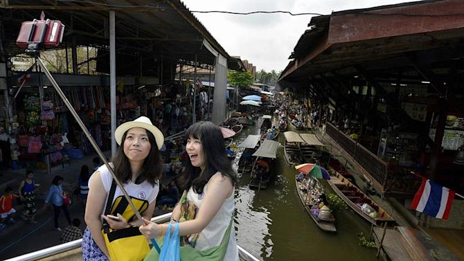 . Ratchaburi (Thailand), 20/02/2015.- A picture made available on 28 February 2015 shows Asian tourists using a selfie stick to picture themselves at the Damnoen Saduak floating market in Ratchaburi province, Thailand, 20 February 2015. Small wooden boats in the market sell fruit, vegetables, flowers and all sorts of cooked food and tourist souvenirs. Most boats in the market are however filled with tourists from all over the world. (Tailandia) EFE/EPA/UDO WEITZ