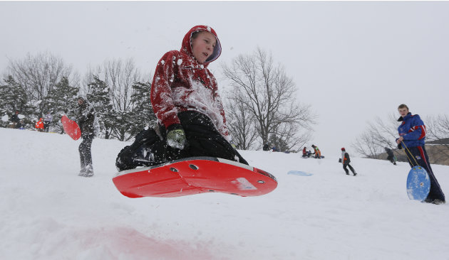 Braden Center jumps his sled over a mound of snow on Thursday, Feb. 21, 2013 in Wichita. Kan. Parts of Kansas have received over a foot of snow since a strong winter storm moved through the area. (AP