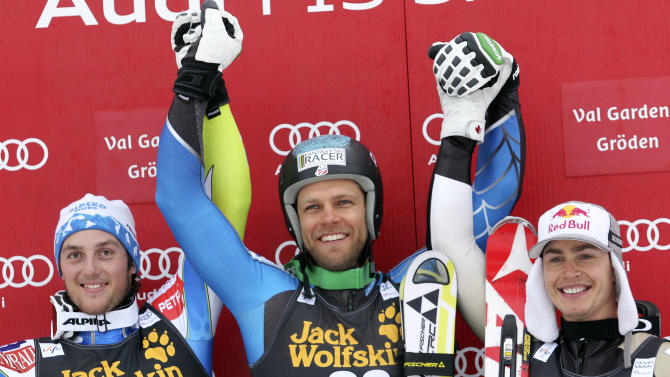 Steven Nyman, of the United States, center, winner of an alpine ski, men's World Cup downhill, celebrates on the podium with second placed Slovenia's Rok Perko, left, and third placed Canada's Erik Guay, in Val Gardena, Italy, Saturday, Dec. 15, 2012. (AP Photo/Alessandro Trovati)